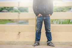 Young fashion man`s legs in jean. And black jacket and sneakers on bridge outdoor Stock Photos