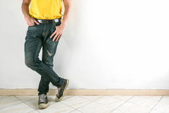 Young fashion man`s legs in jeans and shoes on tile floor. Royalty Free Stock Image