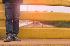 Young fashion man`s legs in jeans. And sneakers on yellow bridge outdoor Stock Photography