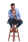 Young fashion man sitting on a chair Stock Photos