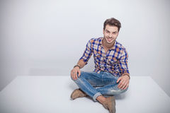 Young fashion man sitting with his legs crossed. Attractive young fashion man sitting with his legs crossed while smiling for the camera Royalty Free Stock Photos
