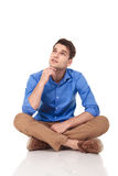 Young fashion man sitting with his legs crossed. While holding his hand to the chin, looking up, thinking Stock Photo