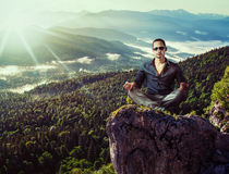 Young fashion man sitting on mountains stone Stock Images