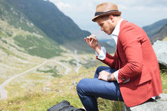 Young fashion man smokes in nature Stock Image