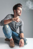 Young fashion man smoking a cigarette. While relaxing on the floor, looking away from the camera Stock Photo