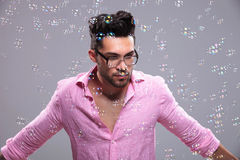 Young fashion man spreads his hands among bubbles Stock Photography