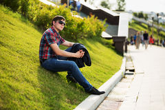 Young fashion man in sunglasses in a city park Stock Photos