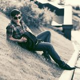 Young fashion man in sunglasses sitting on grass in city park Stock Images