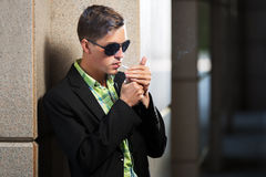 Young fashion man in sunglasses smoking a cigarette Stock Photography