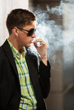 Young fashion man in sunglasses smoking a cigarette Royalty Free Stock Photos