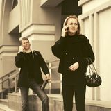 Young fashion man and woman with handbag calling on cell phone royalty free stock image
