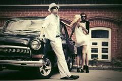 Young fashion man and women next to vintage car Royalty Free Stock Images