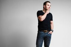 A young fashion model. A young male fashion model wearing jeans and a black shirt Stock Photography