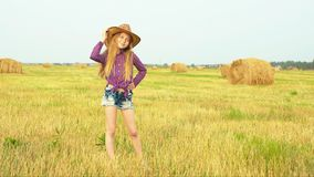 Young fashion model in cowboy hat posing on harvesting field in autumn village. Teenager girl in cowgirl look poing for. Young fashion model in cowboy hat posing stock video