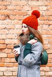 Young fashion model girl posing with bag of coffee and a warm wi. Nter clothes near the red brick wall Stock Image