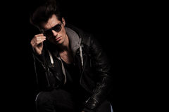 Young fashion model in leather jacket taking off his sunglasses Royalty Free Stock Photos