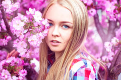 Young fashion model in pink blooming flowers Stock Images