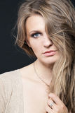 Young fashion model posing on dark background. Stock Image