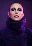 Young fashion model posing in studio. Bald. Bright make up. Royalty Free Stock Image