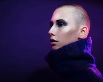 Young fashion model posing in studio. Bald. Bright make up. Royalty Free Stock Photography