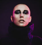 Young fashion model posing in studio. Bald. Bright make up. Stock Photo