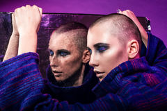 Young fashion model posing in studio. Bald. Bright make up. Royalty Free Stock Images