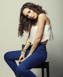 Young fashion model sitting on chair Stock Photo