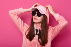 Young fashion model teenage girl posing at studio in stylish pink hoody, cap and balck sunglasses, keeps hands on hood. Casual stock photos