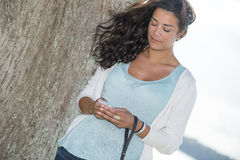 Young fashion model woman checking short messages outdoors. Attractive young fashion model looking at smart phone in nature near to a big tree Royalty Free Stock Images