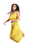 Young fashion model in yellow dress jumps in mid air. Stock Photo