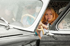 Young fashion people driving retro car in the rain Stock Images