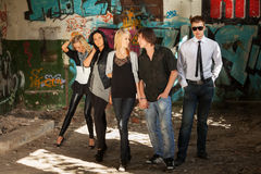 Young fashion people at the graffiti wall Royalty Free Stock Photography