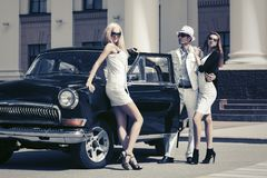 Young fashion people outside a vintage car. In city street Royalty Free Stock Photos