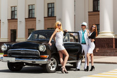 Young fashion people at the retro car Royalty Free Stock Photos
