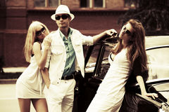 Young fashion people by retro car Royalty Free Stock Photos
