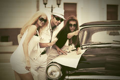 Young fashion people with a road map next to vintage car Stock Photography