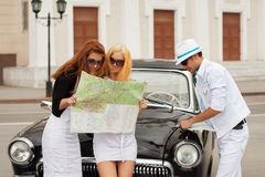 Young fashion people with a road map at retro car Royalty Free Stock Photos
