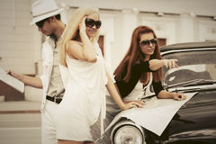 Young fashion people with a road map by retro car Royalty Free Stock Photo