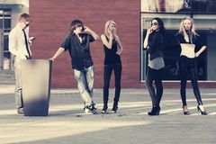 Young fashion people using cell phones on city street stock image