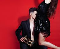 Young fashion style couple man and woman on red sexy background,. Luxury stuff, lifestyle modern people sale concept close up Royalty Free Stock Images