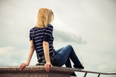 Young fashion woman against a cloudy sky Royalty Free Stock Image