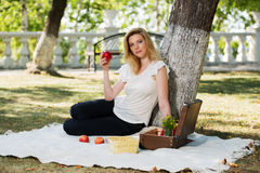 Young fashion woman with apple in a city park Royalty Free Stock Image