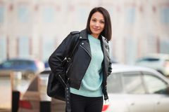 Young fashion woman in black leather jacket walking in city street Royalty Free Stock Photography
