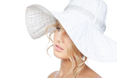 Young fashion woman in a big hat posing in studio Stock Image