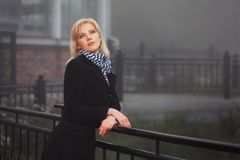 Young fashion woman in black coat leaning on handrail in a fog Royalty Free Stock Photo
