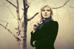 Young fashion woman in black coat walking in a fog outdoor Stock Photography