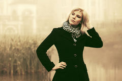 Young fashion woman in black coat walking in a fog outdoor Royalty Free Stock Image