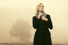 Young fashion woman in black coat walking in a fog outdoor. Young fashion blond woman in black coat walking in a fog outdoor Royalty Free Stock Photos