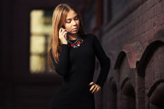 Young fashion woman in black dress calling on cell phone Stock Photography