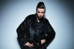 Young fashion woman in black fur coat posing Stock Photography